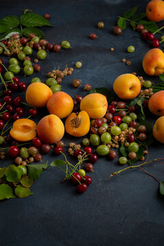 Summer berries and fruits on dark background