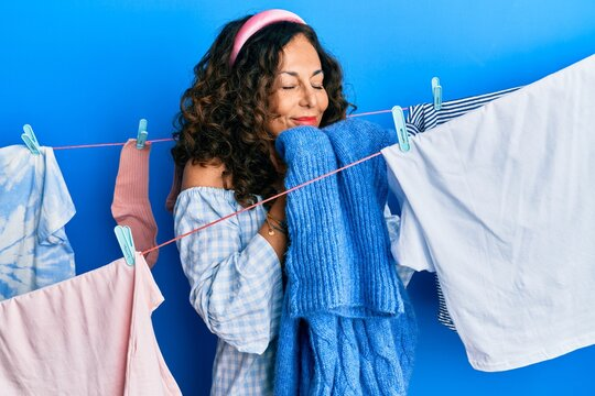 Hispanic middle age woman doing laundry smelling scent from clean clothes