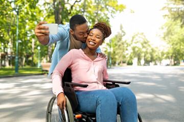 Obraz Romantic black man and his impaired girlfriend in wheelchair taking selfie together, kissing at city park - fototapety do salonu