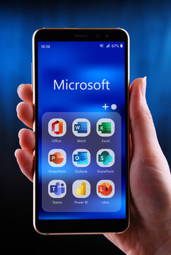 Hand holding smartphone displaying a set of Microsoft programs