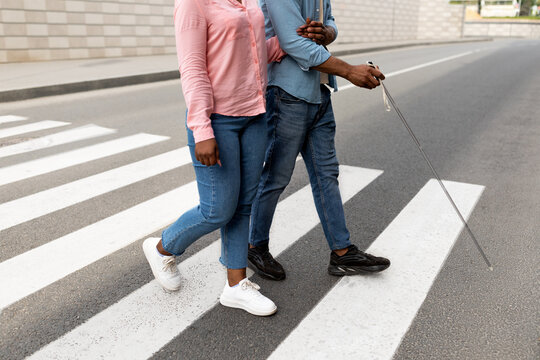 Cropped view of female caregiver assisting visually impaired black man with cane cross city street, closeup