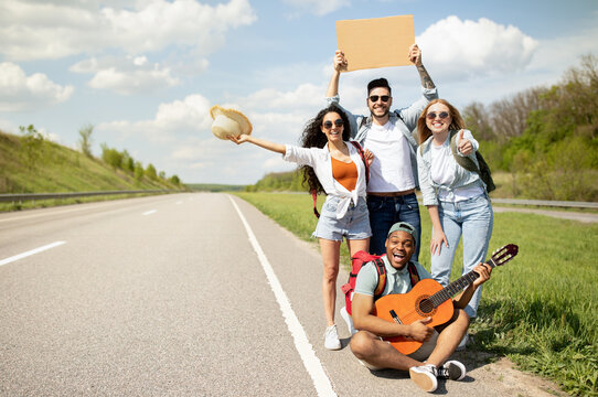 Joyful multiethnic friends thumbing their ride on highway with empty sign, playing guitar, going on autostop journey