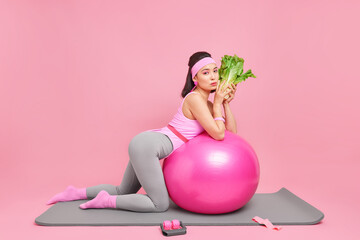 Obraz Sideways shot of serious motivated dark haired Asian sportswoman leans at swiss ball holds green vegetable eats healthy food leads active lifestyle has regular workout to be fit poses on fitness mat - fototapety do salonu