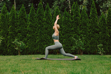 Obraz young woman practicing yoga on the grass in the garden - fototapety do salonu
