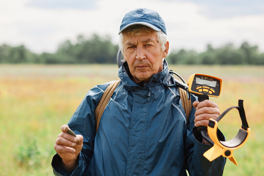 Senior numismatist with coin in hand and metal detector over shoulders looking directly at camera after finding historical artifacts in ground in field.