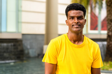 Obraz Portrait of handsome black African man wearing yellow t-shirt outdoors in city during summer while smiling - fototapety do salonu