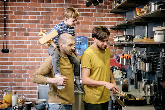 Two happy gay men and little boy cooking in kitchen environment