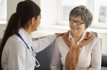 Fototapeta Kind female doctor consulting reassuring giving psychological support senior patient gently put her hand on shoulder. Medical service and checkup meeting at private clinic closeup portrait obraz