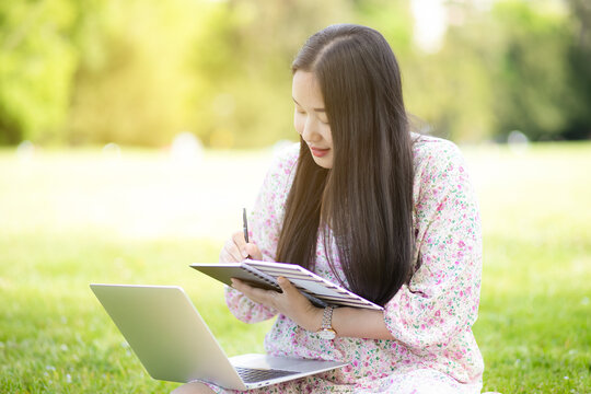 Working outside in summer or spring and WFH concept, Young beautiful Asian woman reading a book and looking laptop in the natural park, Freelance working, homeschooling, distance learning.
