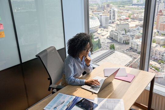 Serious focused African American businesswoman top manager sitting at desk working typing on laptop computer in modern corporate office near panoramic window. Business technologies concept. Top shot.