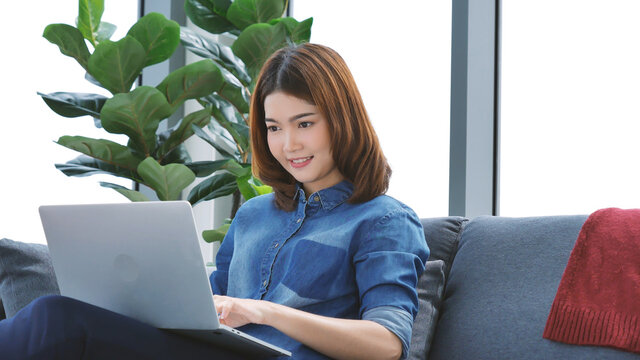 Woman working from home on laptop online meeting in home office. Entrepreneur asian business woman using notebook laptop sit on sofa technology new normal lifestyle. Happy woman typing keyboard laptop