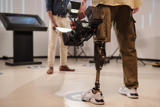 Cameraman with robotic leg standing in front of African guy in studio