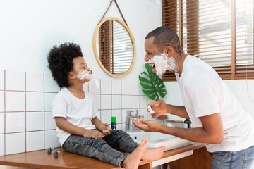 Obraz Funny Black African American Father and little boy laughing while playing shaving foam on their face in bathroom at home on holiday. Happy African family having fun - fototapety do salonu