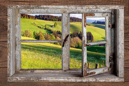 Blick aus einem rustikalen Holzfenster in die Landschaft