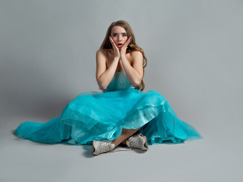 beauty in shock, a young beautiful blonde in a lush blue dress
