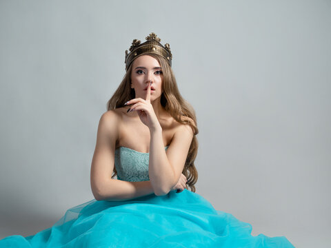 fairy princess in a crown holds her finger to her lips, shhh, it's a secret.