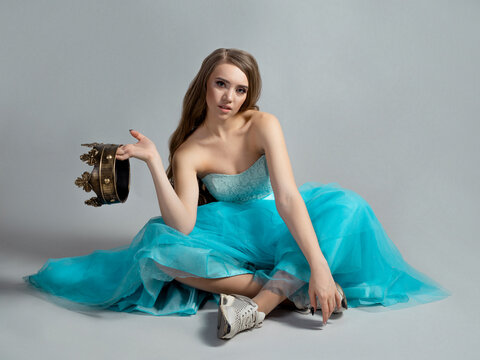 Modern princess, beauty in a crown and a lush blue dress and sneakers,