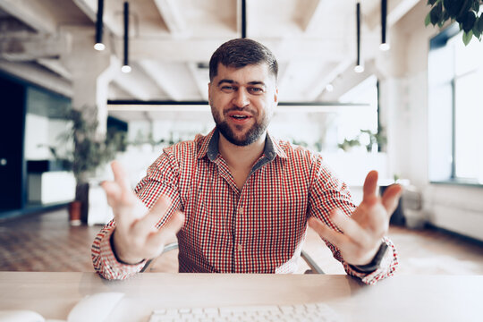 Joyful young businessman sitting at desk looking at camera