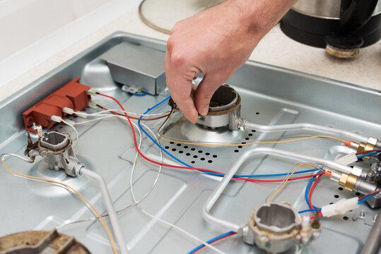 man hand repairs hotplate of gas panel