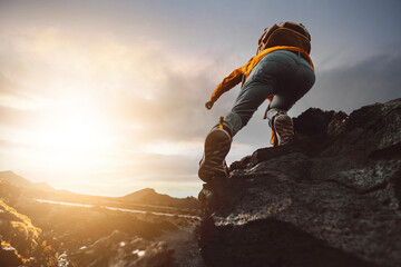 Fototapeta Successful hiker hiking a mountain pointing to the sunset. Wild man with backpack climbing a rock over the storm. Success, wanderlust and sport concept.  obraz