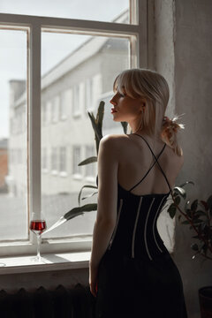 Retro portrait sexy blonde woman in black dress, vintage interior woman posing at window. Sensual romantic look, girl relaxes at home