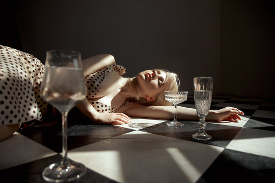 Woman with glass alcohol in hand lies on floor, an old interior, romantic look blonde girl. Shadow of window on woman body
