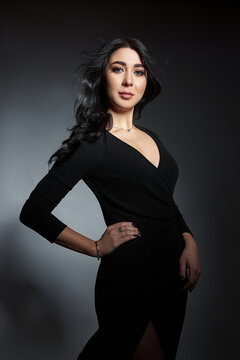 Beautiful brunette woman in a black dress poses in the studio. Elegant girl with beautiful natural makeup