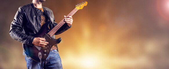 Fototapeta Rock guitarist plays an electric guitar. Artist and musician performs like rockstar. Guitar player performs on stage. obraz