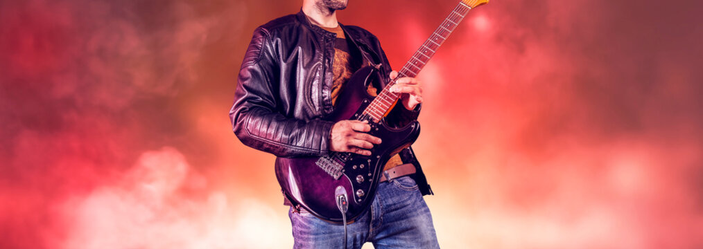 Rock guitarist plays solo on an electric guitar. Artist and musician performs like rockstar. Guitar player performs on stage.