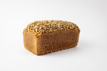 Bochenek chleba ze słonecznikiem na białym tle.
