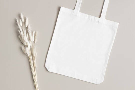 White tote bag mockup with a lagurus decoration on the beige background.