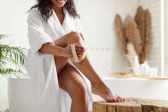 Unrecognizable Black Woman Dry Brushing Legs Sitting On Bathtub Indoor