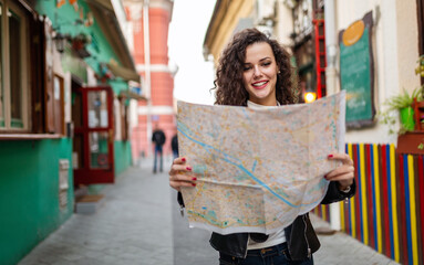 Cheerful woman searching direction on location map while traveling