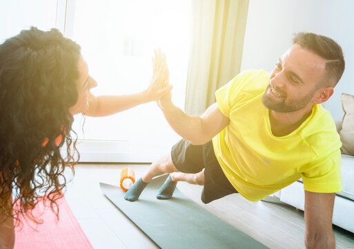 Young couple trains together in their living room in the morning giving high five - health and wellness concept - warm filter on background.