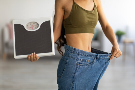 Closeup of Indian woman in oversized jeans holding scales, showing results of weight loss program or liposuction at home