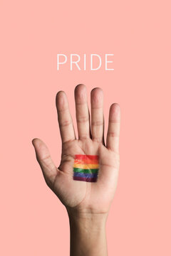 hand with a rainbow pride flag and text pride