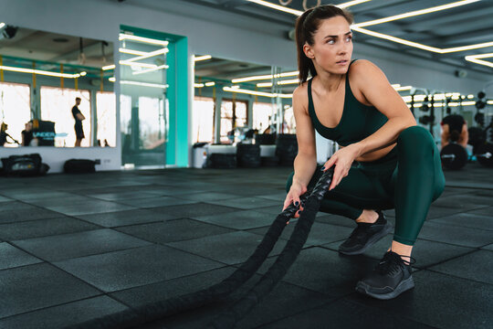 White sportswoman doing workout with battle ropes in gym