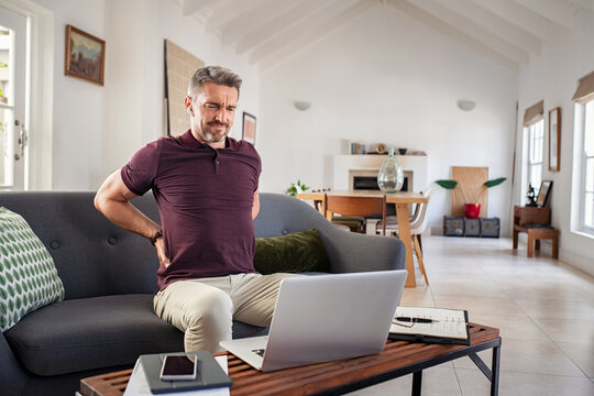 Mature man stretching back while working at home