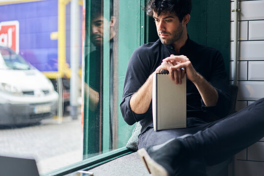 Brunet man in deep thought looking ahead and holding notepad with pen