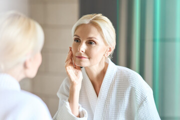Obraz Gorgeous mid age adult 50 years old blonde woman standing in bathroom after shower touching face, looking at reflection in mirror doing morning beauty routine. Older dry skin care concept. - fototapety do salonu
