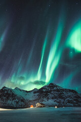 Aurora borealis, Northern lights with stars glowing on snowy mountain in the night sky on winter at Lofoten Islands