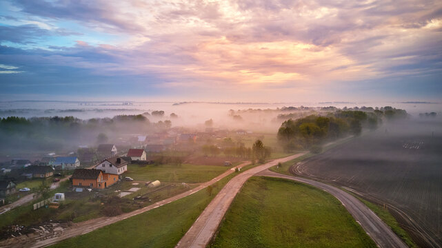 Aerial view of village, rural dirt road and trees covered by fog. Early misty morning sunrise panorama
