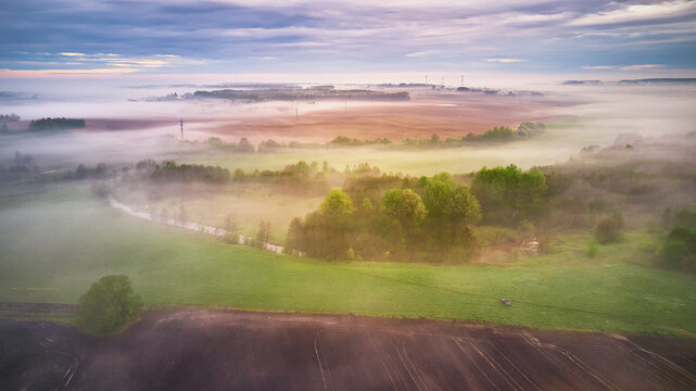 Summer cloudy rainy foggy morning panorama. Rural misty river, fields, meadow, village.