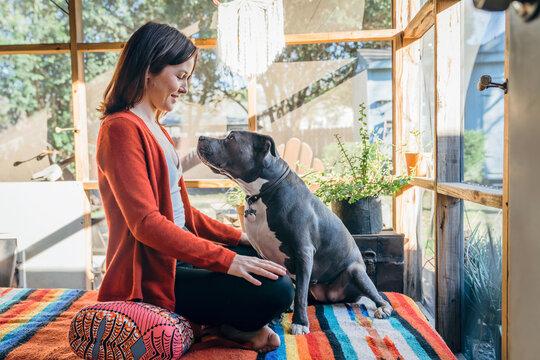 Woman sitting smiling at her Pitbull pet dog