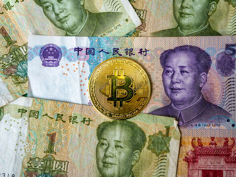 China Banknotes and Bitcoin Crypto Currency side by side. A battle rages which is a better store of value, digital versus fiat losing purchasing power. Bitcoin slowly dominating but faces regulation