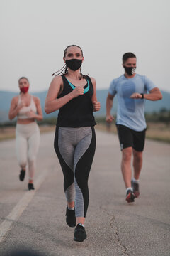 Multiethnic runners group wear face masks running keep social distance outdoor. Fit healthy diverse team wears sportswear jogging in evening on nature sports track distancing for safety.