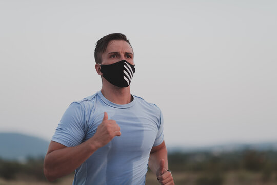 Fitness man in wet sporty clothes wearing black protective face mask running outdoors in the city during coronavirus outbreak. Covid 19 and physical jogging activity sport and fitness. New normal