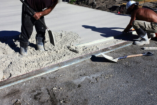 Unrecognizable builders working together on leveling cement