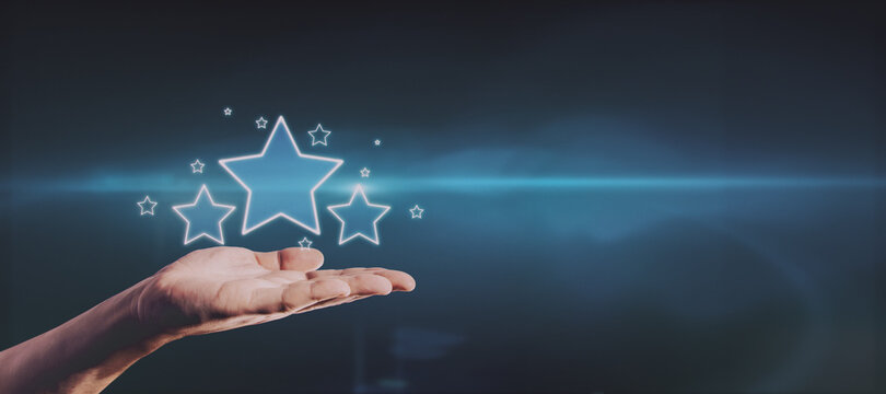 Hand holding glowing stars on blue background with mockup place for your advertisement. Customer feedback and ranking concept.