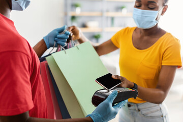 Fototapeta African Woman Paying Courier With Phone Receiving Shopping Bags Indoors obraz